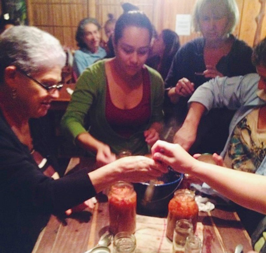Cloudbridge researchers teaching local women how to make their own salsa.